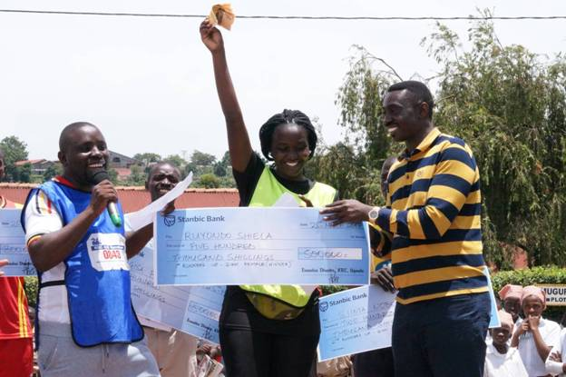 The Chief Guest Mr. Robert Issabalija, the Permanent Secretary Ministy of Health handing over a cheque of 500,000 to Ms Ruyondo Sheila the winner of the Women 21 Kilometer marathon