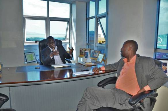 Hon. Alex Ruhunda(Left) stresses a point during the interview in his state of the art office at DAJ Towers in Fort Portal. Right is Mr. John Murungi, the interviwer.